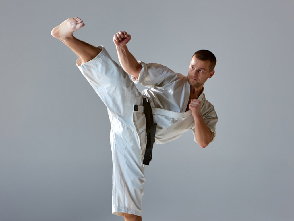 A martial artist dressed in white kicking one leg out in front of him.