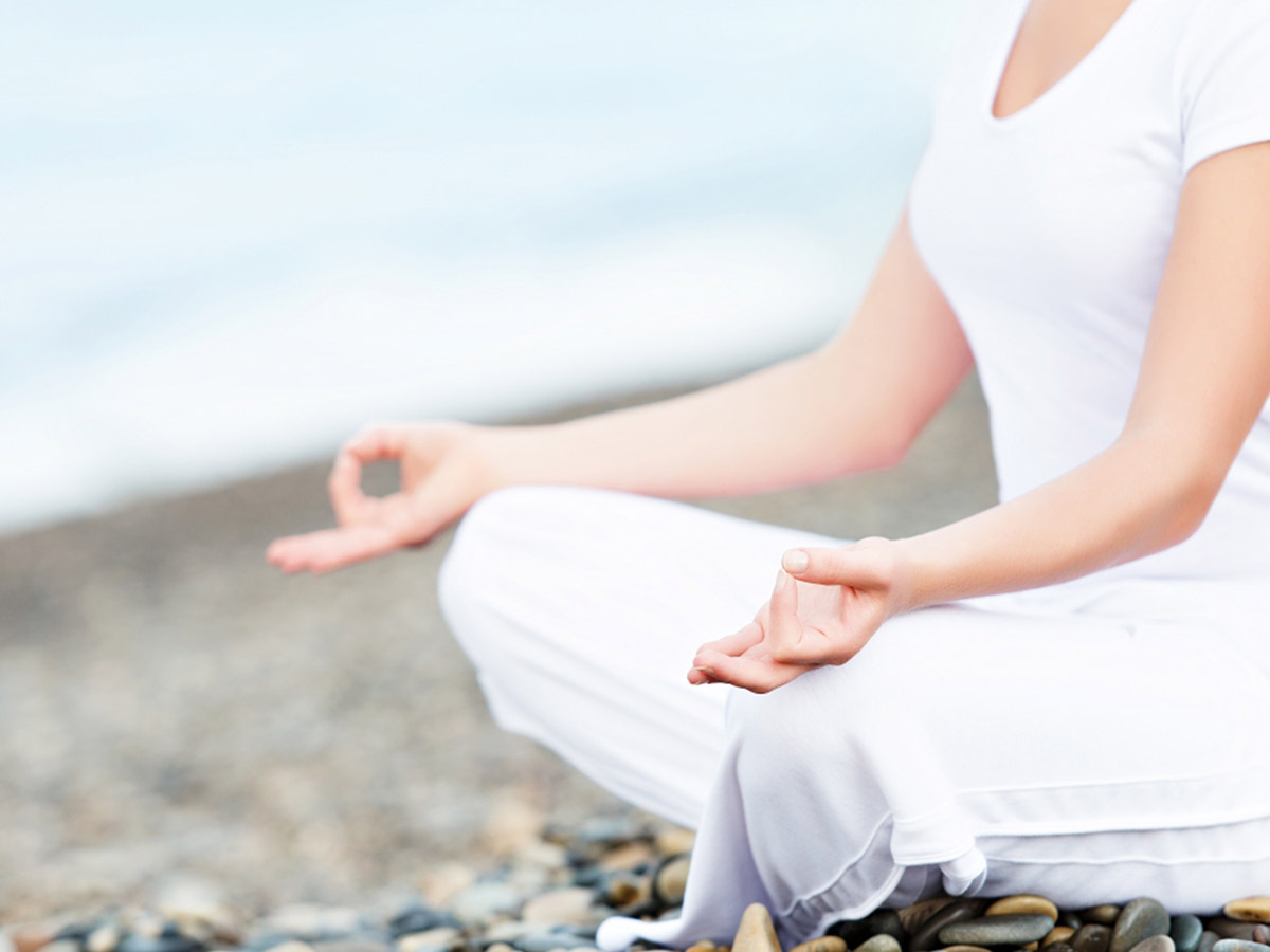 Woman dressed in white sitting on a rocky shoreline meditating.