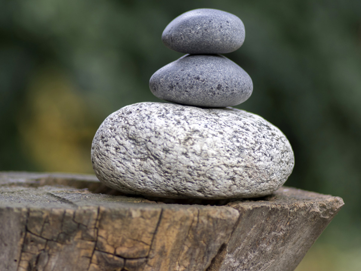 Three river stones balanced on top of a piece of wood.