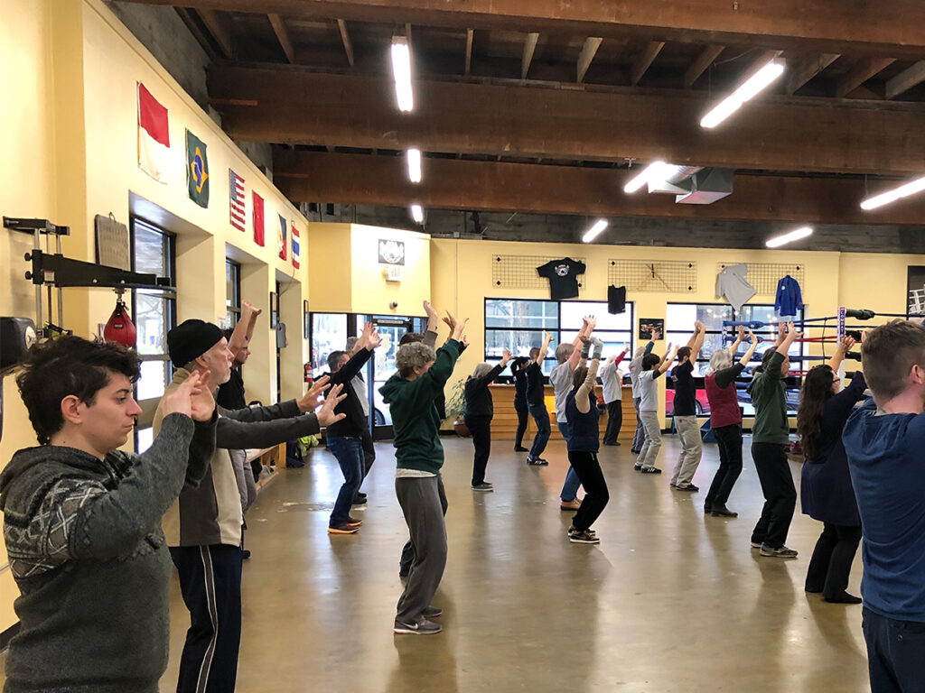 A large tai chi class with their hands up in the air learning tai chi.