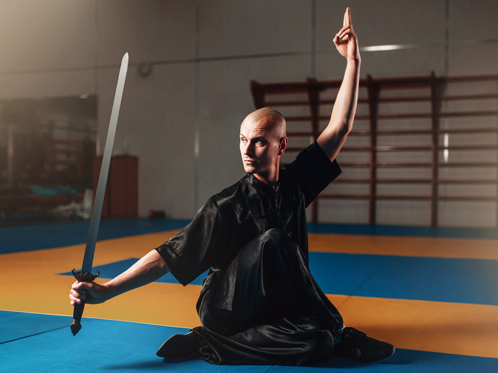 A martial artist dressed in a black outfit resting on the ground with one hand in the air and the other hand holding a sword vertically in front of him.