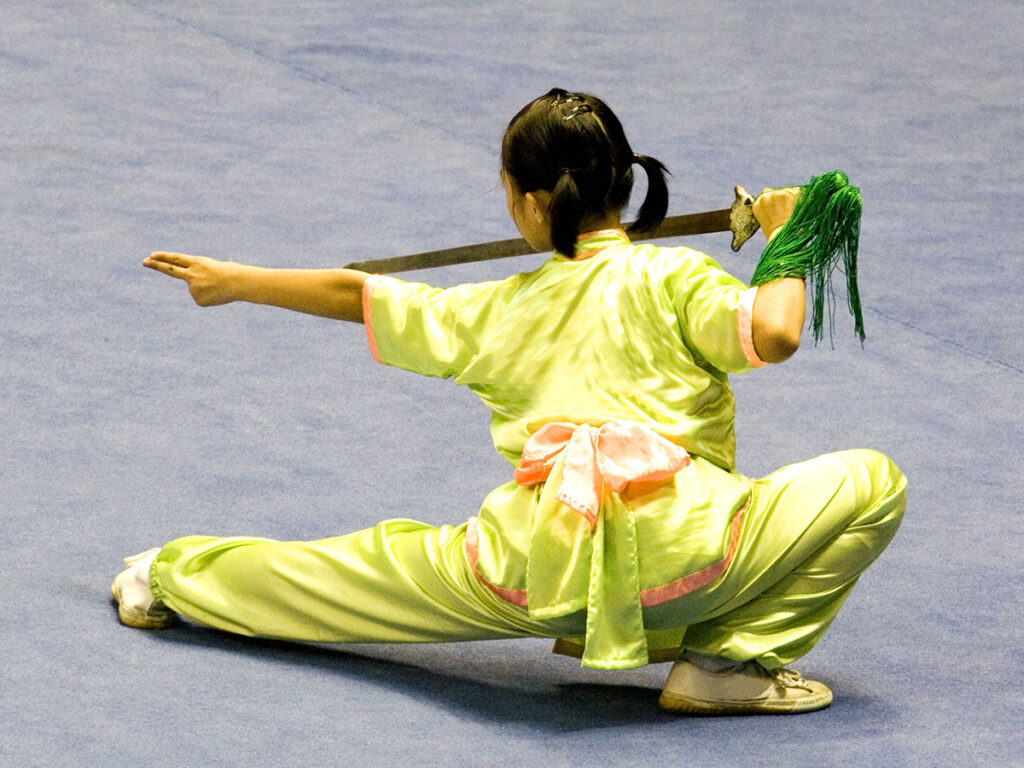 A girl in a yellow uniform with her leg out in front of her holding out a sword.