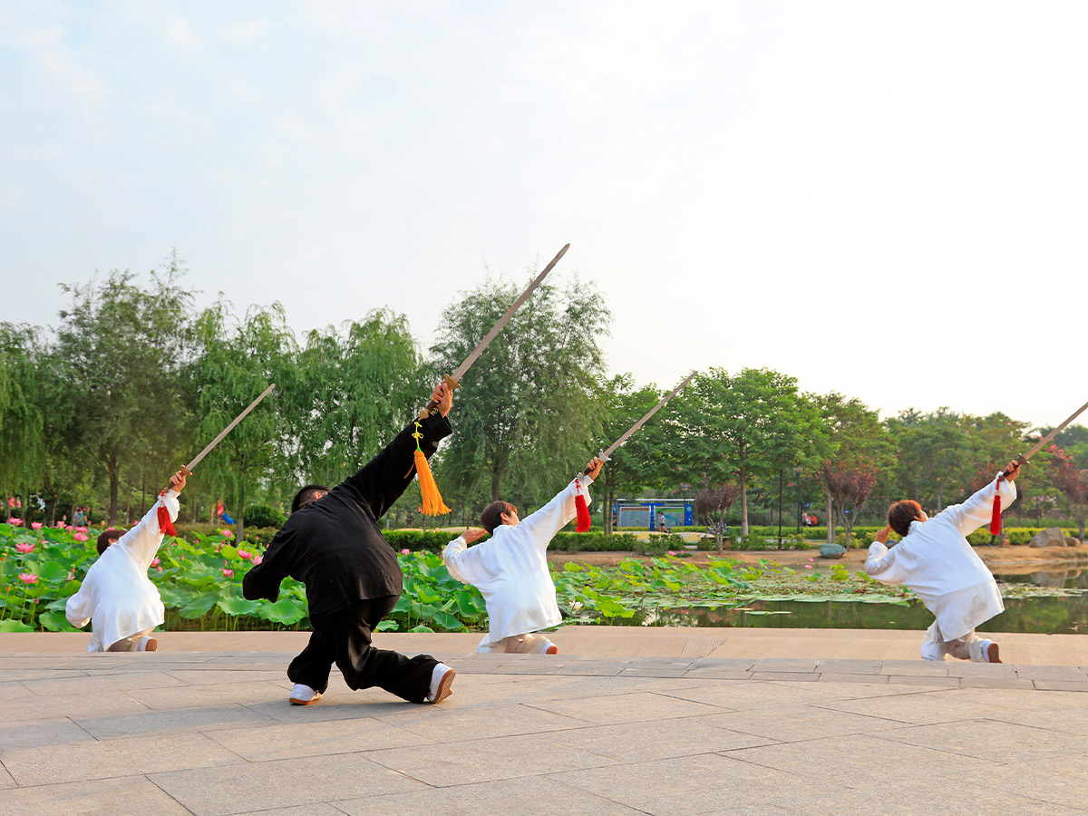 An image of three people doing a tai chi pose.
