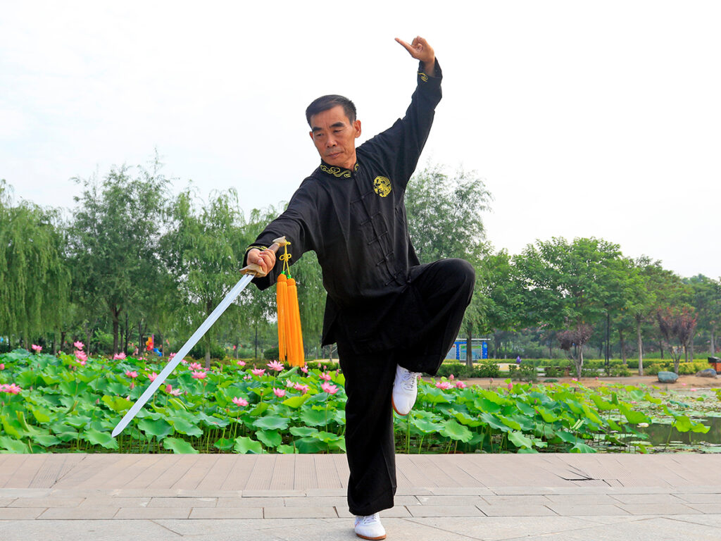 A martial artist standing outside, balancing on one leg with the other leg bent and a sword held out at a downward angle in front of him.