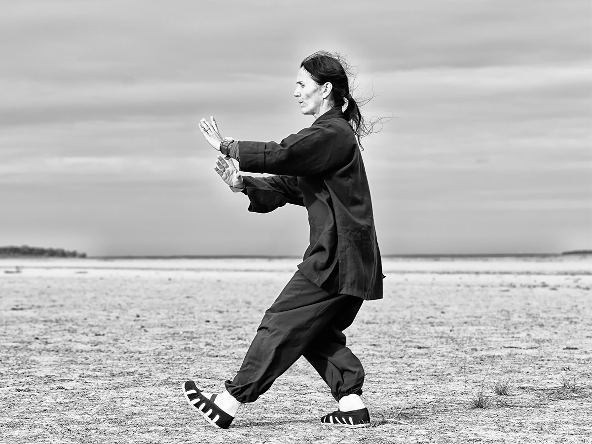 An image of a woman doing tai chi by a lake.