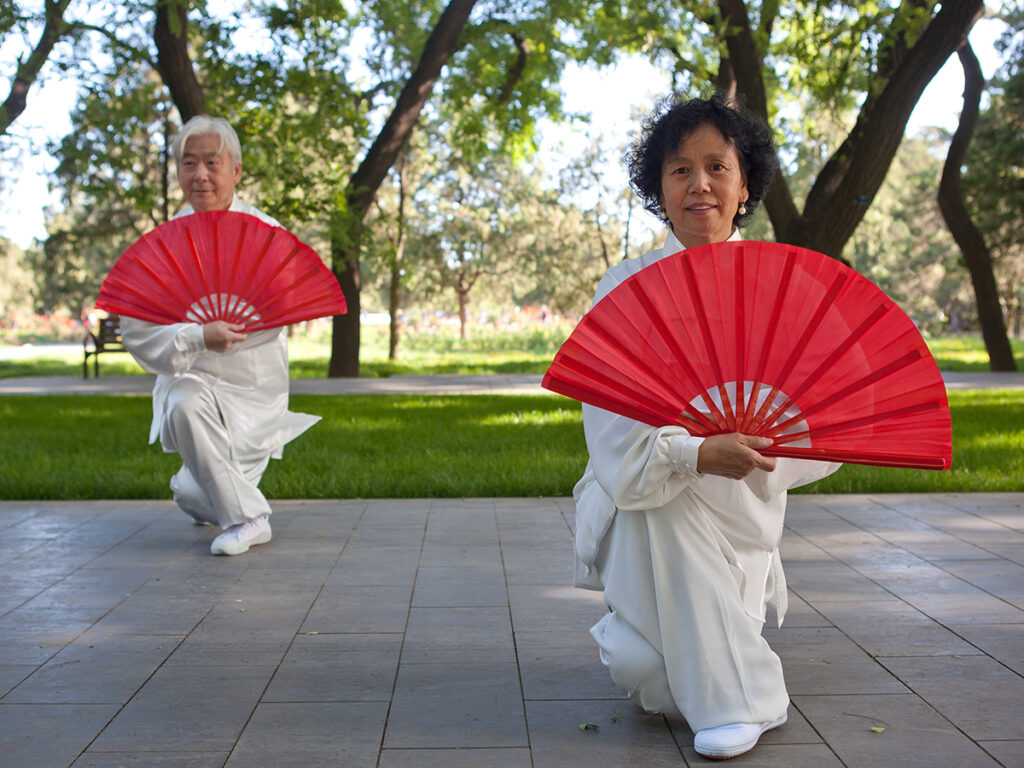 Two martial artists outside, a man and a woman, bent down towards the ground in white outfits holding opened red fans out in front of them.