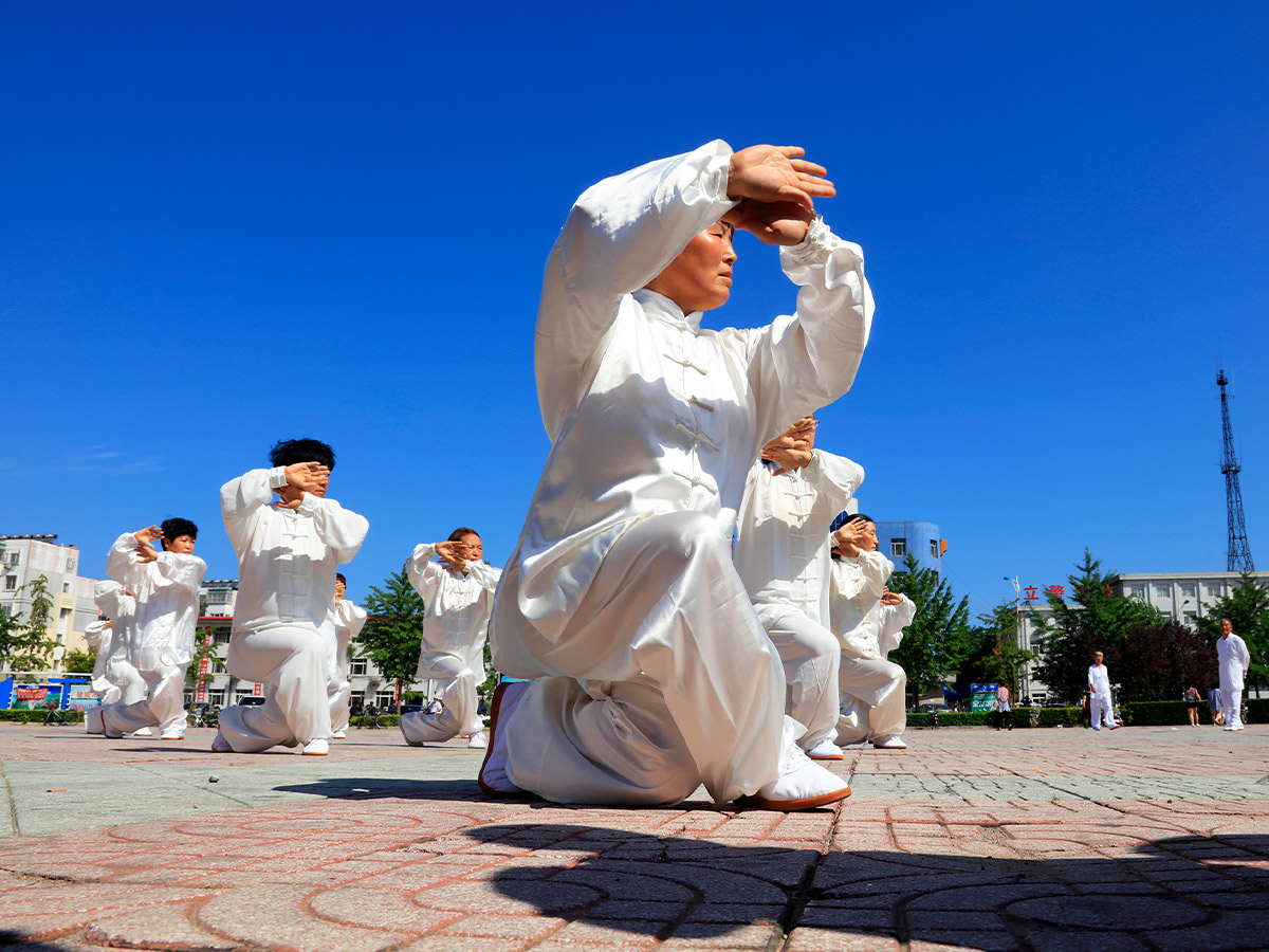 An image of a man in white doing a Tai Chi pose